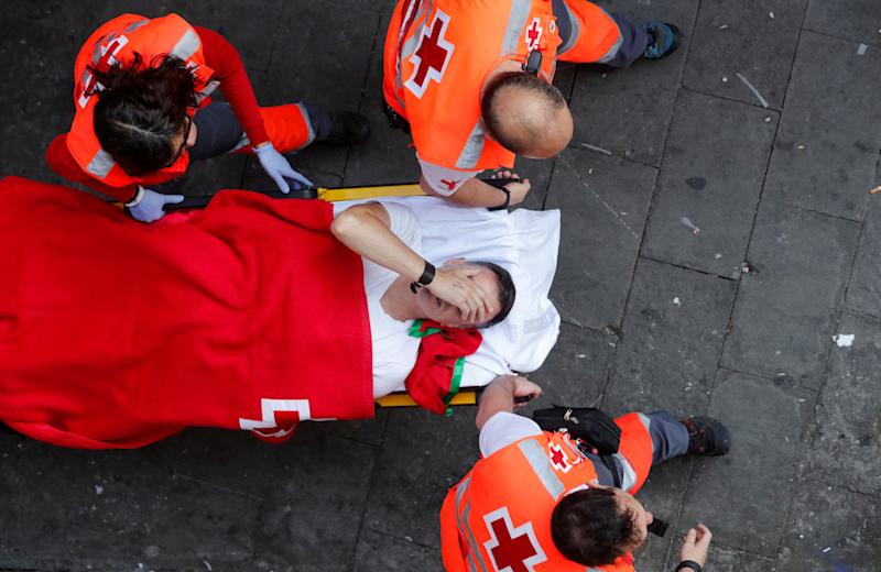 A reveller is helped by medical staff during the running of the bulls at the San Fermin festival in Pamplona, Spain, July 11, 2019. (Photo: Susana Vera/Reuters)