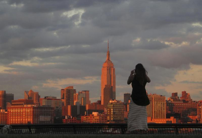 A woman stops to photograph the skyline of New York across from the Empire State Building as she walks in a park along the Hudson River in Hoboken