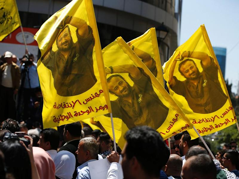 Protesters in Ramallah waving flags bearing a portrait of Marwan Borghouti (Abbas Momani/Getty Images)