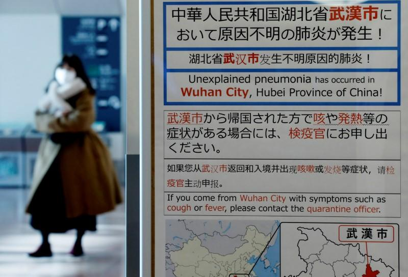 A woman wearing a mask walks past a quarantine notice about the outbreak of coronavirus in Wuhan, China at an arrival hall of Haneda airport in Tokyo