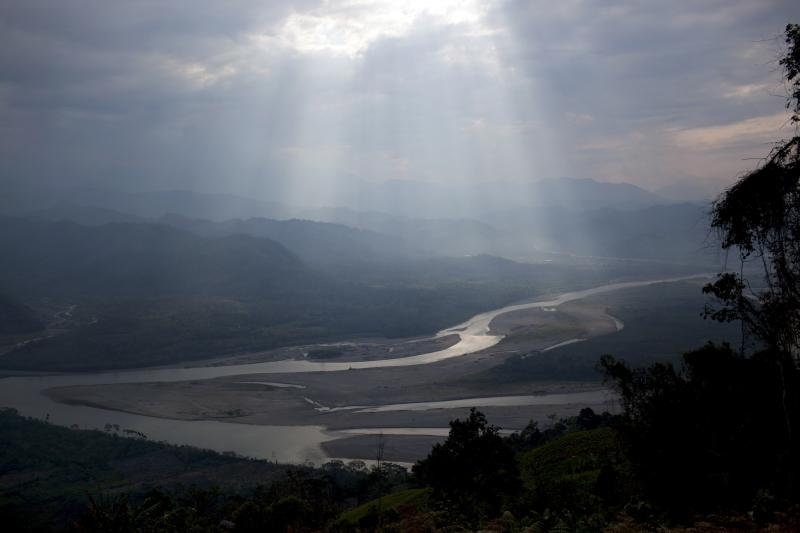 In this Sept. 28, 2013 photo, sunlight filteres through the clouds, illuminating the Apurimac river in Pichari, Peru. The river cuts through a long valley that the United Nations says yields 56 percent of Peru's coca leaves. The government says it will soon begin destroying coca crops in the region, known as the VRAE - the Valley of the Apurimac and Ene rivers. (AP Photo/Rodrigo Abd)