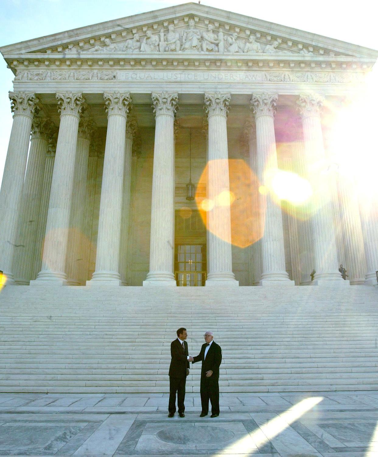 Chief Justice John Roberts (left) and Justice Stevens pose for photographers outside the U.S. Supreme Court after Roberts' investiture ceremony on Oct. 3, 2005.