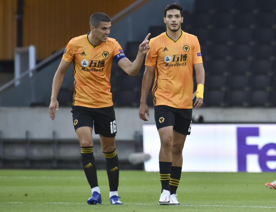Wolverhampton Wanderers' Raul Jimenez, right, talks with his captain Conor Coady after scoring his team's first goal from the penalty spot during the Europa League round of 16 second leg soccer match between Wolves and Olympiakos at Molineux Stadium in Wolverhampton, England, Thursday, Aug. 6, 2020. (AP Photo/Rui Vieira)