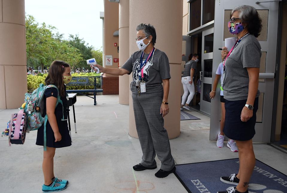 A school employee checks the temperature of a student as she returns to school on the first day of in-person classes in Orange County at Baldwin Park Elementary School on August 21, 2020 in Orlando, Florida, US. Face masks and temperature checks are required for all students as Florida's death toll from COVID-19 now exceeds 10,000, with some teachers refusing to return to their classrooms due to health concerns. (Photo by Paul Hennessy/NurPhoto via Getty Images)