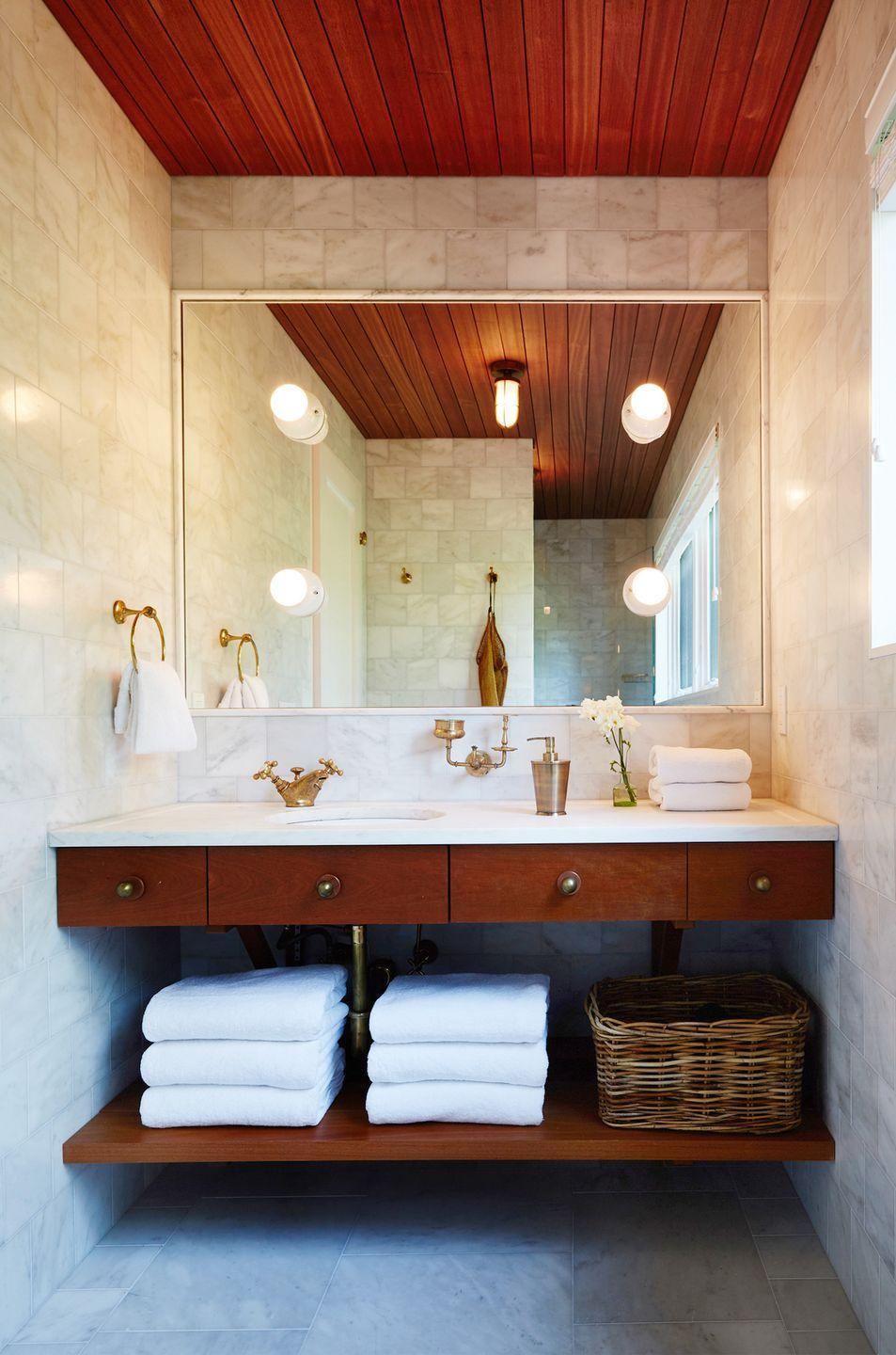 """<p>This Montauk bathroom designed by <a href=""""http://www.robertmckinley.com/residential#/mckinley-bungalow-federal/"""" rel=""""nofollow noopener"""" target=""""_blank"""" data-ylk=""""slk:Robert McKinley Studio"""" class=""""link rapid-noclick-resp"""">Robert McKinley Studio</a> feels both woodsy and intimate, expansive and cosmopolitan. That's thanks to the minimalist color palette that lets the materials do the talking and nods to the surrounding environment, like the nautical pendant lamp, long, parallel wood panels, and glossy natural stone tiles. </p>"""