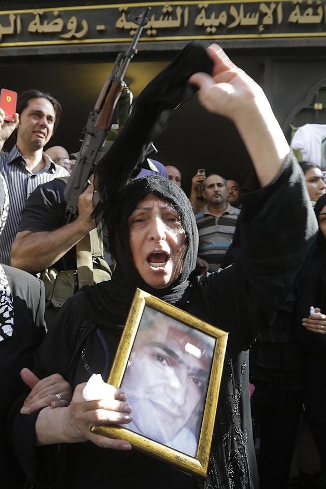 A Lebanese Shiite women mourns during the funeral procession of Hamad al-Mekdad, 42, who was killed on Thursday by a car bomb explosion, during his funeral procession at an predominantly Shiite area and stronghold of the Lebanese militant group Hezbollah in the southern suburb of Beirut, Lebanon, Friday, Aug. 16, 2013. Lebanese forensic experts collected evidence Friday at the scene of a massive explosion in a southern suburb of Beirut that killed dozens of people and wounded hundreds, the deadliest blast in the area in nearly three decades. (AP Photo/Hussein Malla)