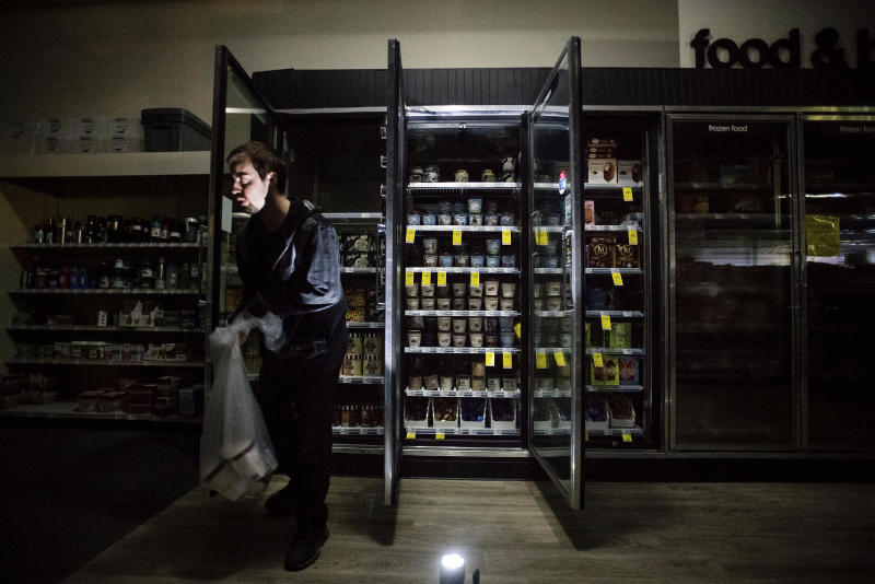 FILE - In this Oct. 9, 2019, file photo, CVS Pharmacy shift supervisor James Quinn throws out ice cream from darkened freezers as downtown Sonoma, Calif., remains without power. Experts say it's hard to know what might have happened had the power stayed on, or if the utility's proactive shutoffs are to thank for California's mild fire season this year. (AP Photo/Noah Berger, File)