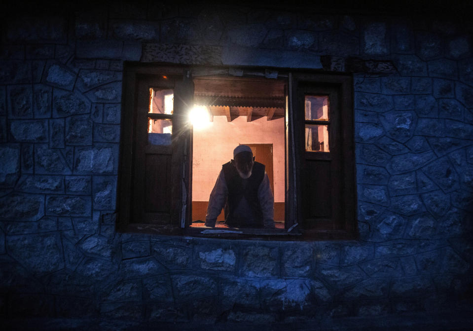 An elderly Kashmiri villager Lal Din, looks out from a window of his home at Dardkhor village, an area that experiences frequent attacks by wild animals, on the outskirts of Srinagar, Indian controlled Kashmir, Monday, Aug. 24, 2020. Amid the long-raging deadly strife in Indian-controlled Kashmir, another conflict is silently taking its toll on the Himalayan region's residents: the conflict between man and wild animals. According to official data, at least 67 people have been killed and 940 others injured in the past five years in attacks by wild animals in the famed Kashmir Valley, a vast collection of alpine forests, connected wetlands and waterways known as much for its idyllic vistas as for its decades-long armed conflict between Indian troops and rebels. (AP Photo/Mukhtar Khan)