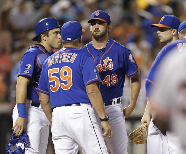 New York Mets pitching coach Dan Warthen (59) talks to Jonathon Niese (49) as David Wright, right, and Travis d'Arnaud, left, listen during the seventh inning of a baseball game against the San Francisco Giants Friday, Aug. 1, 2014, in New York. (AP Photo/Frank Franklin II)
