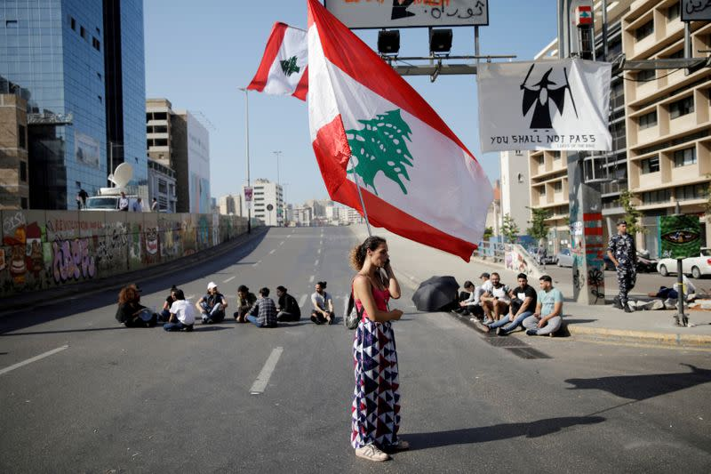 FILE PHOTO: A woman holds a Lebanese flag as she stands at a roadblock during ongoing anti-government protests in Beirut