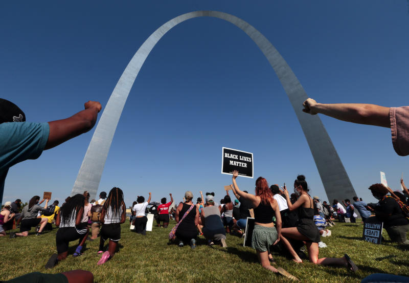Participants raise their fists in solidarity during a moment of silence for those lost to police brutality, under the Gateway Arch during a rally in St. Louis on Sunday, June 14, 2020. (Robert Cohen/St. Louis Post-Dispatch via AP)