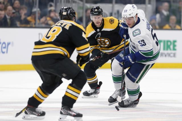 Vancouver Canucks' Bo Horvat (53) brings the puck into the zone as Boston Bruins' Matt Grzelcyk (48) and Charlie Coyle (13) defend during the third period of an NHL hockey game in Boston, Tuesday, Feb. 4, 2020. (AP Photo/Michael Dwyer)