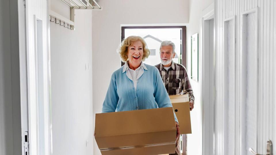 Senior Couple Carrying Boxes Into New Home on Moving Day.