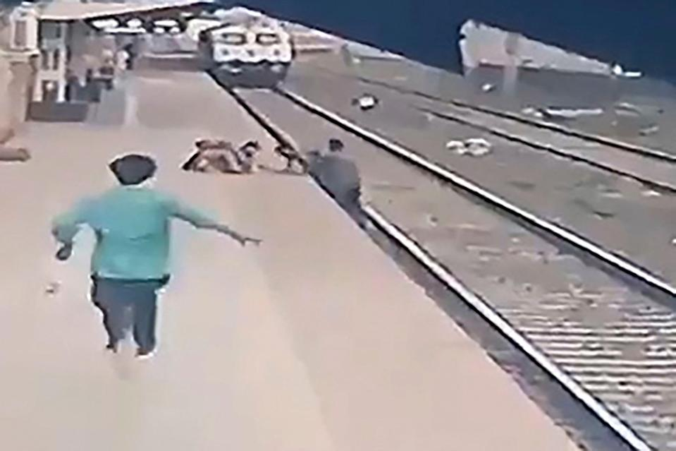 <p>This video frame grab taken from footage released by Indian Ministry of Railways on 20 April, 2021, shows a pointsman (R) saving a child (top C) as he lost his balance and fell in the path of an oncoming train at Vangani railway station in Mumbai</p> (Indian Ministry of Railways /AFP via Getty Images)
