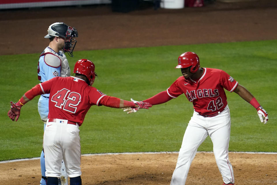 Los Angeles Angels' Justin Upton, right, celebrates his grand slam at home plate with Luis Rengifo during the seventh inning of a baseball game against the Minnesota Twins Friday, April 16, 2021, in Anaheim, Calif. (AP Photo/Marcio Jose Sanchez)