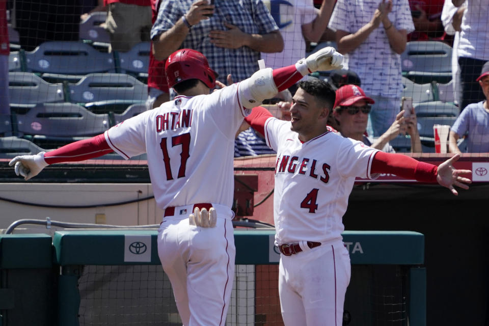 Los Angeles Angels' Shohei Ohtani, left, is congratulated by Jose Iglesias after hitting a solo home run during the fifth inning of a baseball game against the Boston Red Sox Wednesday, July 7, 2021, in Anaheim, Calif. (AP Photo/Mark J. Terrill)