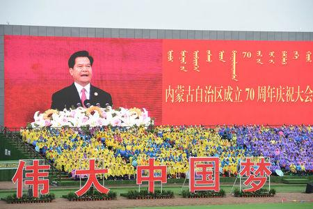 """A giant screen shows Li Jiheng, secretary of the Communist Party of China (CPC) Committee of Inner Mongolia autonomous region, speaking during a celebration to mark the 70th anniversary of the establishment of the Inner Mongolia autonomous region, in Hohhot, Inner Mongolia autonomous region, China August 8, 2017. The Chinese characters read, """"great Chinese dream"""". CNS/Hou Yu via REUTERS"""