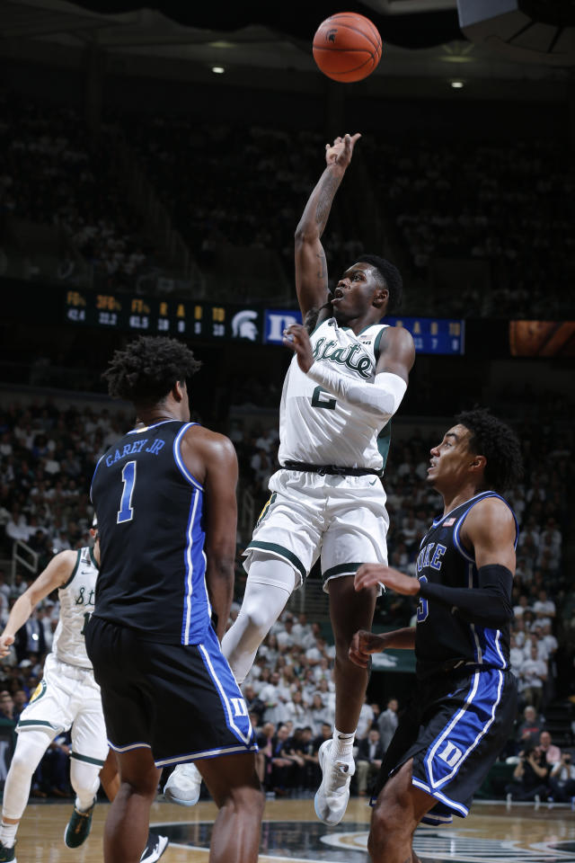 Michigan State's Rocket Watts, center, puts up a shot against Duke's Vernon Carey Jr., left, and Tre Jones, right, during the second half of an NCAA college basketball game, Tuesday, Dec. 3, 2019, in East Lansing, Mich. (AP Photo/Al Goldis)