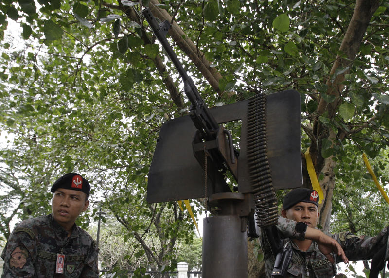 Philippine policemen stay beside a machine gun as they secure an area in front of the U.S. Embassy in Manila, Philippines on Thursday Sept. 13, 2012. Manila police tightened security in the area following an attack that killed the U.S. ambassador and three other Americans in Libya. (AP Photo/Aaron Favila)