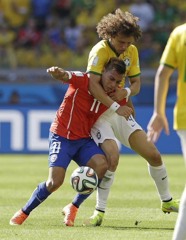 Brazil's David Luiz holds Chile's Eduardo Vargas as they struggle for the ball during the World Cup round of 16 soccer match between Brazil and Chile at the Mineirao Stadium in Belo Horizonte, Brazil, Saturday, June 28, 2014. (AP Photo/Ricardo Mazalan)