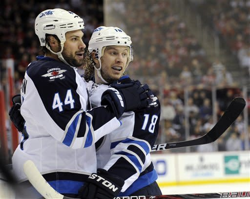 Winnipeg Jets' Zach Bogosian (44) celebrates his goal with Bryan Little during the first period of an NHL hockey gameNew Jersey Devils Sunday, Feb. 24, 2013, in Newark, N.J. (AP Photo/Bill Kostroun)