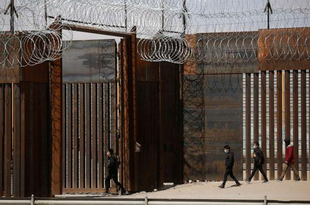 PHOTO: Migrants walk to a gate in the border wall after crossing the Rio Bravo river to turn themselves in to U.S. Border Patrol agents to request for asylum in El Paso, Texas, U.S., as seen from Ciudad Juarez, Mexico, March 14, 2021.  (Jose Luis Gonzalez/Reuters)