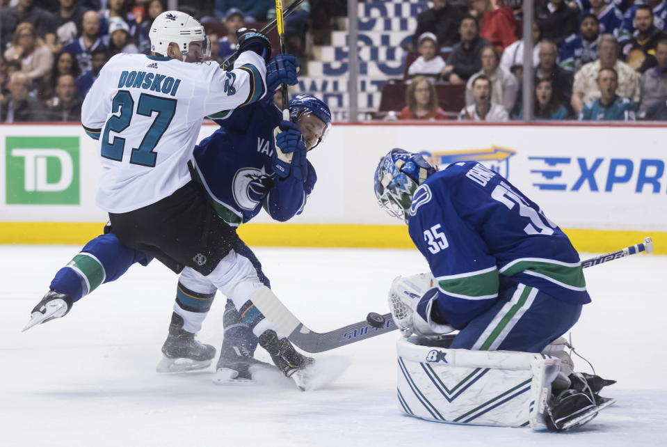Vancouver Canucks goalie Thatcher Demko (35) makes the save as Alex Biega, back right, and San Jose Sharks' Joonas Donskoi, of Finland, collide during the first period of an NHL hockey game in Vancouver, British Columbia, Tuesday April 2, 2019. (Darryl Dyck/The Canadian Press via AP)