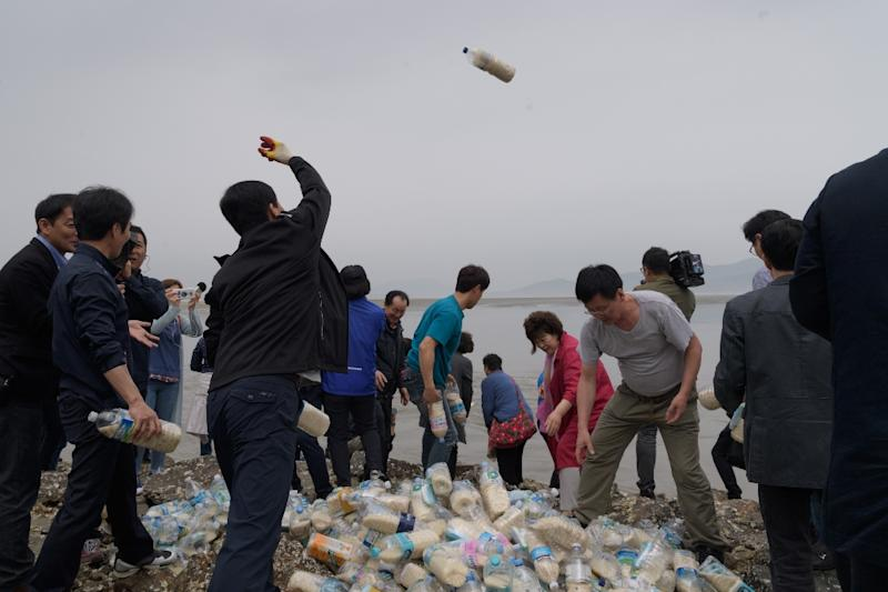 The defectors have been throwing hundreds of bottles filled with food, cash, medicine and memory sticks into the sea twice a month for more than two years (AFP Photo/Ed JONES)