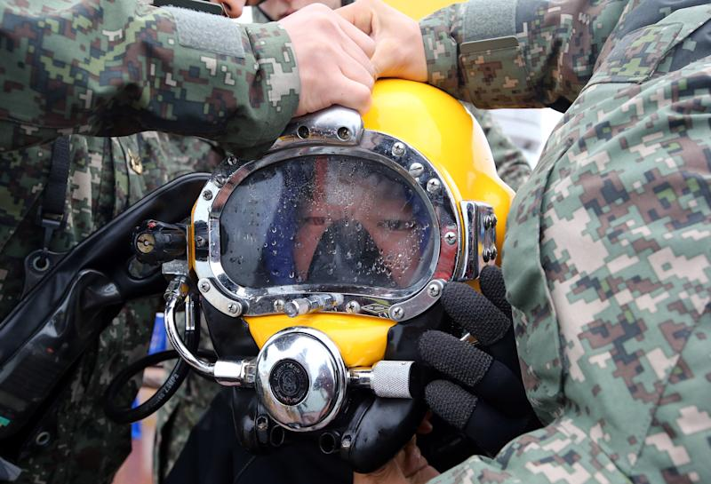 A diver wears a helmet to look for people still missing from the sunken ferry Sewol, in the water off the southern coast near Jindo, South Korea, Saturday, April 26, 2014. A prosecutor investigating the South Korean ferry sinking that left 302 people dead or missing says all 15 crew members involved in the ship's navigation are now in custody. (AP Photo/Yonhap) KOREA OUT