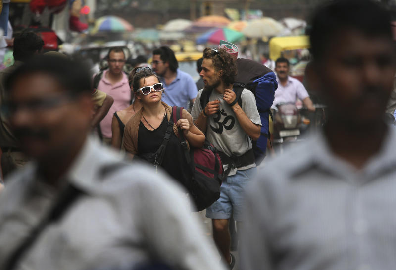 In this Tuesday, April 2, 2013 photo, foreign tourists look for a hotel near the railway station in New Delhi, India. Violence against women, and the huge publicity generated by recent attacks here, is threatening India's $17.7 billion tourism industry. A new study shows tourism has plunged, especially among women, since a 23-year-old Indian student was raped on a New Delhi bus and later died from her injuries, a case that garnered worldwide publicity. (AP Photo /Manish Swarup)