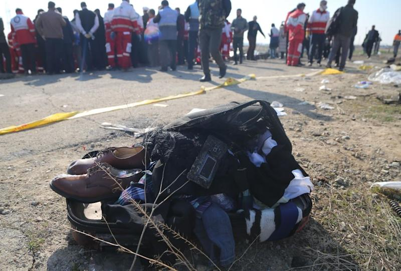 Belongings of passengers are brought from the site by search and rescue team members. Source: Getty