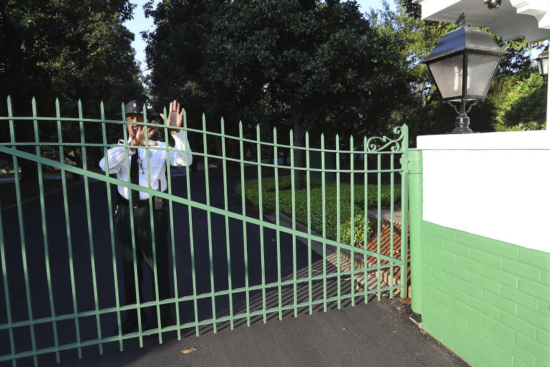 A guard at the main gate to Augusta National Golf Club on Magnolia Lane warns away visitors on what would have been the first practice round for the Masters golf tournament, Monday, April 6, 2020, in Augusta, Ga. The 2020 Masters, postponed because of the coronavirus pandemic, is slated to take place on Nov. 12-15. (Curtis Compton/Atlanta Journal-Constitution via AP)