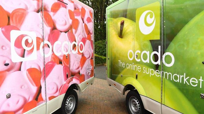 File photo dated of Ocado delivery vans - the one on the left decorated with photos of bright pink pig-shaped sweets, the one on the right with green apples
