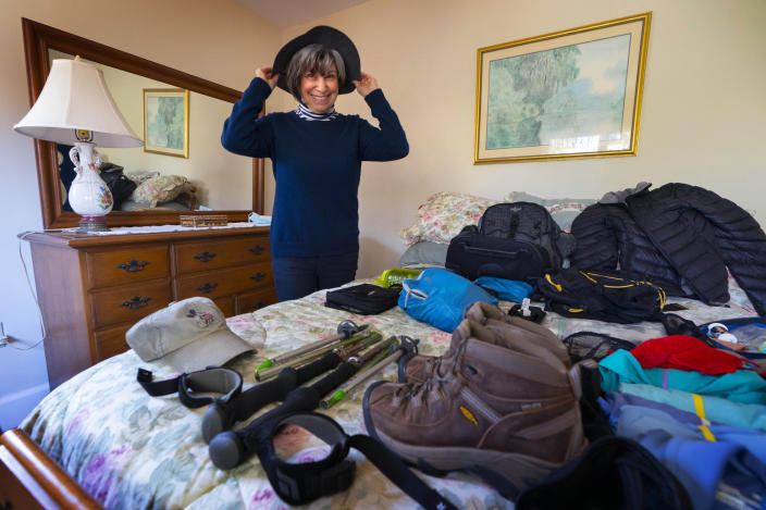 Cindy Charest tries on her sun hat while arranging her hiking gear at her home, Wednesday, March 17, 2021, in Westbrook, Maine. The avid traveler is looking forward to resuming her travels now that she and her husband have been vaccinated for COVID-19. Spring has arrived, and many older adults who have been vaccinated are emerging from hibernation imposed by the coronavirus pandemic. (AP Photo/Robert F. Bukaty)