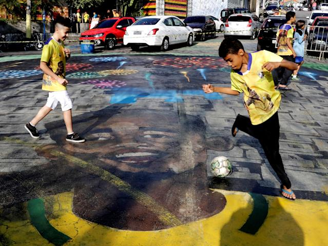 Children play soccer on a street painted with the image of Brazilian soccer player Gabriel Jesus in the neighbourhood where Gabriel Jesus lived in his childhood in Sao Paulo, Brazil June 17, 2018. REUTERS/Paulo Whitaker
