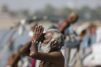 A Hindu man offers prayers at the confluence of rivers Ganges and Yamuna in Prayagraj, India, Sunday, April 25, 2021. After having largely tamed the virus last year, India is in the throes of the world's worst coronavirus surge and many of the country's hospitals are struggling to cope with shortages of beds, medicines and oxygen. (AP Photo/Rajesh Kumar Singh)