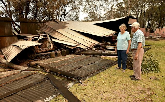 "Art Murphy (R) and his wife Shirley look at a burnt-out section of their property which was caught in bushfires in Old Bar, 350km north of Sydney on November 11, 2019. A state of emergency on November 11 was declared and residents in the Sydney area were warned of ""catastrophic"" fire danger as Australia girded for a fresh wave of deadly bushfires that have ravaged the drought-stricken east of the country. (Photo by PETER PARKS / AFP) (Photo by PETER PARKS/AFP via Getty Images)"