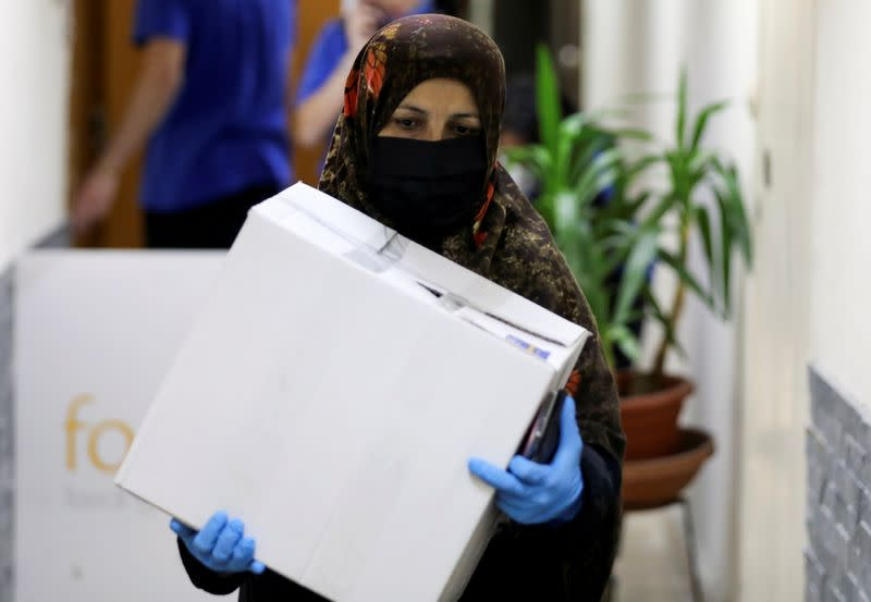 FILE PHOTO: A woman carries a box containing food from FoodBlessed, as the spread of the coronavirus disease (COVID-19) continues, in Beirut