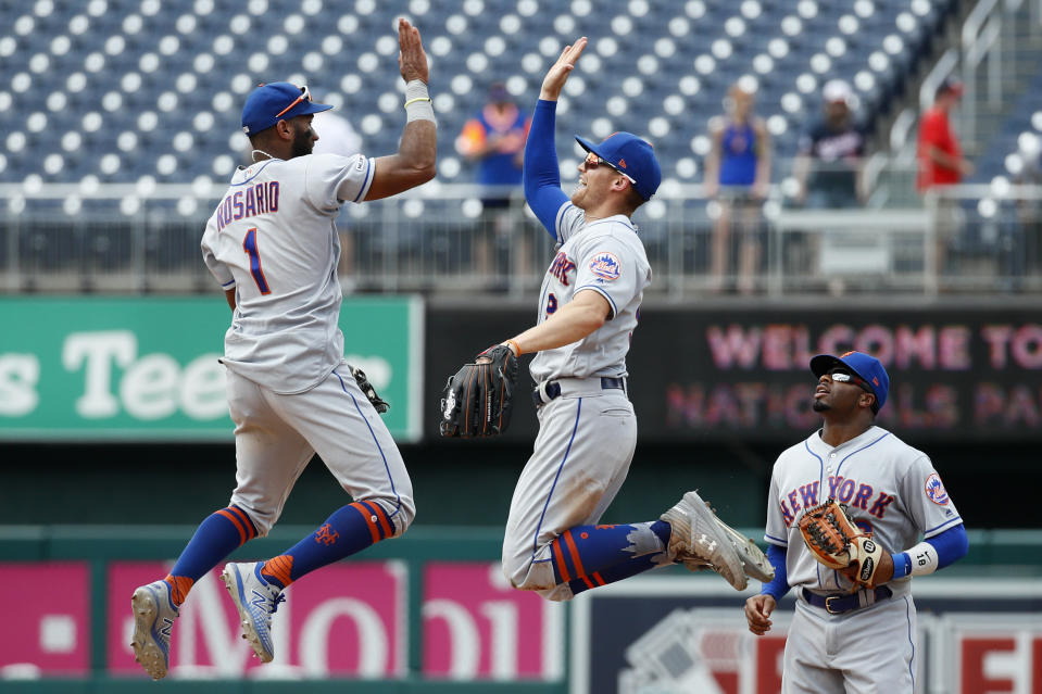 New York Mets' Amed Rosario, left, and Brandon Nimmo high-five in front of teammate Rajai Davis after a baseball game against the Washington Nationals, Wednesday, Sept. 4, 2019, in Washington. New York won 8-4. (AP Photo/Patrick Semansky)