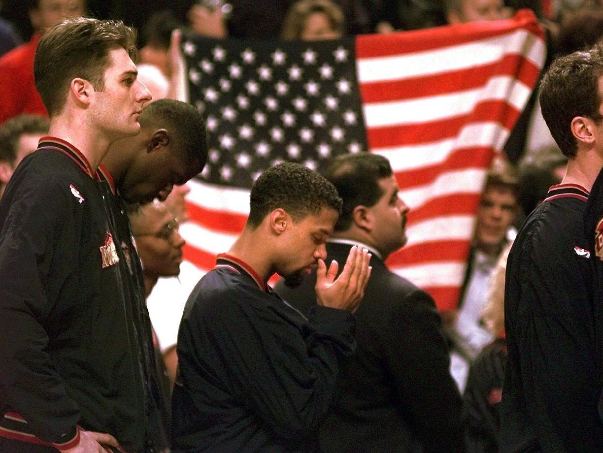 """FILE - In this March 15, 1996 file photo, Denver Nuggets guard Mahmoud Abdul-Rauf stands with his teammates and prays during the national anthem before an NBA basketball game against the Chicago Bulls in Chicago. This was Abdul-Rauf's first game back since he was suspended by the NBA on March 12, 1996, for refusing to participate in the national anthem pre-game ceremony. San Francisco 49ers quarterback Colin Kaepernick's decision this week to refuse to stand during the playing of the national anthem as a way of protesting police killings of unarmed black men has drawn support and scorn far beyond sports. Through the years, """"The Star-Spangled Banner"""" has become a symbol of both patriotism and politics. (AP Photo/M. Spencer Green, File)"""