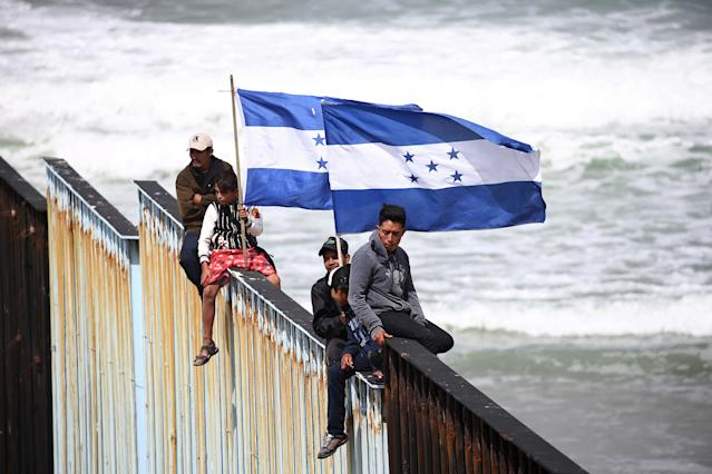 <p>Members of a caravan of migrants from Central America hold Honduran flags while sitting on the border fence between Mexico and the U.S. as a part of a demonstration, prior to preparations for an asylum request in the U.S., in Tijuana, Mexico April 29, 2018. (Photo: Edgard Garrido/Reuters) </p>