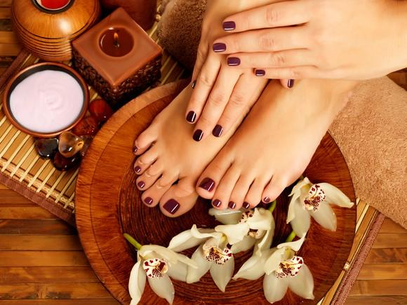 A person's hands and feet on the ground after a manicure and pedicure.