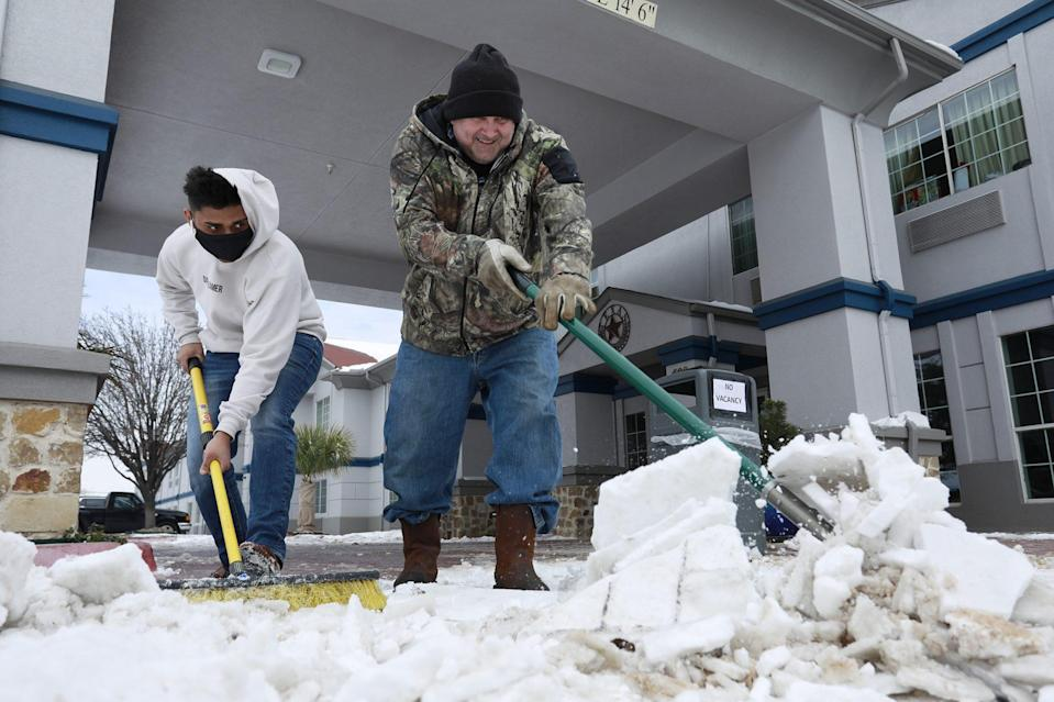 <p>Sam Patel (left) and Mike Bollin (right) clear snow from the front of the SureStay Plus Hotel. The hotel, located in Benbrook, Texas, is completely full with guests who have no power at home. </p>