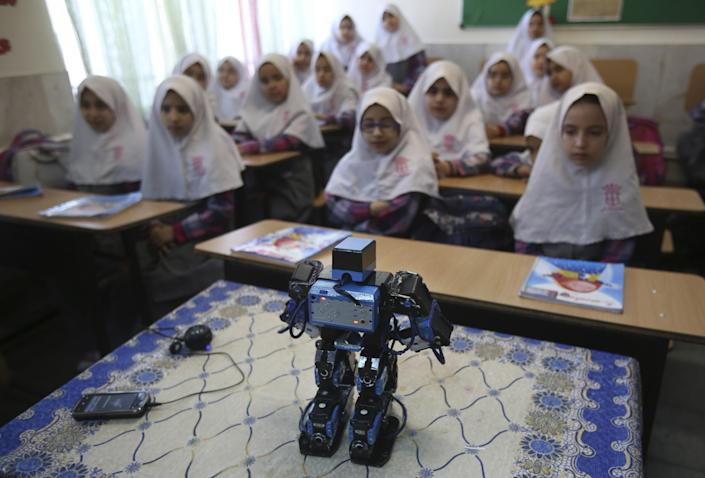 """In this picture taken on Monday, Feb. 24, 2014, Veldan, a humanoid praying robot which is built by Iranian schoolteacher Akbar Rezaie, performs morning prayer in front of Alborz elementary school girls in the city of Varamin some 21 miles (35 kilometers) south of the capital Tehran, Iran. Rezaei who has built a robot to show to children how to execute daily prayers, has innovated an amusing way of encouraging young children to say their daily prayers by using the science of robotics. Out of personal interest and unrelated to his field of study, Akbar Rezaei attended private robotics classes and acquired the skill of assembling and developing customized humanoid robots. He built the robot at home with basic tools and gave it the designation """"Veldan"""", a term mentioned in Quran meaning: """"Youth of Heaven"""". By applying some mechanical modifications such as adding up two extra engines Akbar Rezaei managed to let the robot perform praying movements, such as prostration, more easily. (AP Photo/Vahid Salemi)"""
