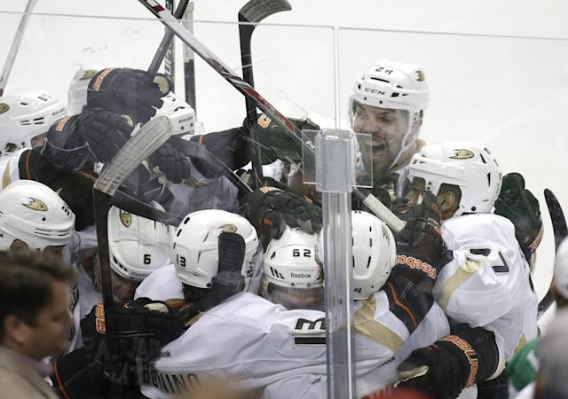 Anaheim Ducks Nick Bonino (13) is mobbed by his teammates after he scored the game winning goal in overtime of Game 6 to win the first-round NHL hockey playoff series against the Dallas Stars in Dallas, Sunday, April 27, 2014. The final score 5-4 for the Ducks. (AP Photo/LM Otero)