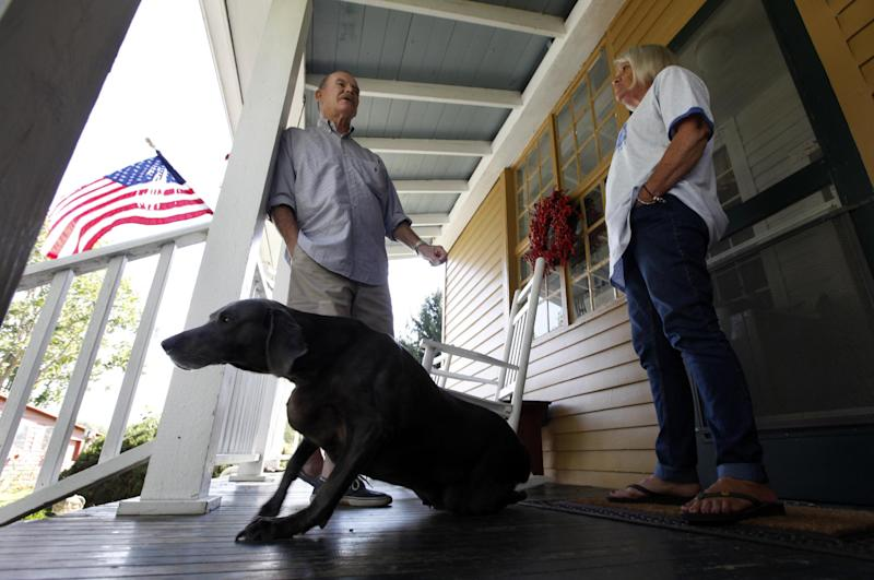 This photo taken Oct. 10, 2012 shows Virginia voter Harry Donahue talking to his wife Nancy on the front porch of their farmhouse, built in the 1700's, in Farmville, Va. Donahue, a 68-year-old retired chemical worker from Philadelphia's New Jersey suburbs, moved to Virginia in 2001 and brought with him an independent streak and a voting pattern that ranges from Ronald Reagan to Ross Perot. He plans to back Obama this year after supporting John McCain in 2008. (AP Photo/Steve Helber)