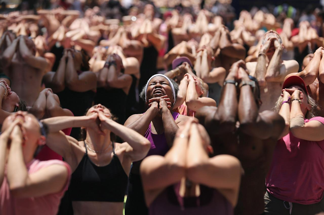 NEW YORK, NY - JUNE 20:  People brave high temperatures while practicing bikram yoga as part of the annual Mind Over Madness event in Times Square on June 20, 2012 in New York City. The free yoga classes are held annually on the summer solstice, the longest day of the year and the first day of summer, amidst the hussle and bustle of Times Square, considered one of the busiest places on earth.  (Photo by John Moore/Getty Images)