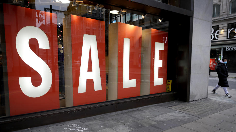 A sale sign in the window of a closed shop on Oxford Street in London, Saturday, Dec. 26, 2020. London is currently in Tier 4 with all non essential retail closed and people have been asked to stay at home, on what is usually one of the busiest retail days of the year with the traditional Boxing Day sales in shops. (AP Photo/Kirsty Wigglesworth)