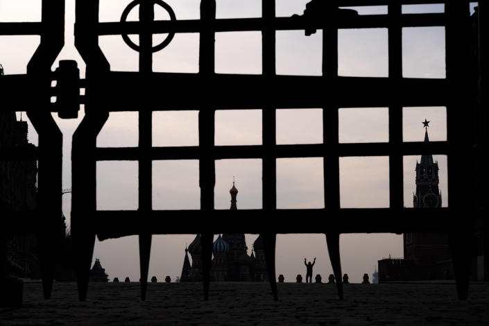 A man gestures in almost empty Red Square with St. Basil's Cathedral, center, and the Spasskaya Tower, right, seen through a part of a lattice of the Nikolsky Gate in Moscow, Russia, Sunday, March 29, 2020. The new coronavirus causes mild or moderate symptoms for most people, but for some, especially older adults and people with existing health problems, it can cause more severe illness or death. (AP Photo/Victor Berezkin)