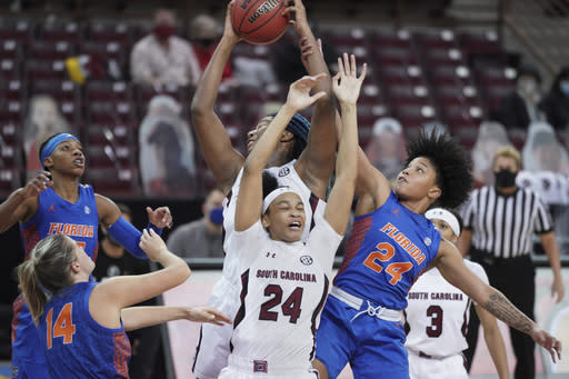 South Carolina forward Aliyah Boston, back, battles for a rebound with teammate LeLe Grissett (24) against Florida guard Yasmeen Chang (24) during the first half of an NCAA college basketball game Thursday, Dec. 31, 2020, in Columbia, S.C. (AP Photo/Sean Rayford)